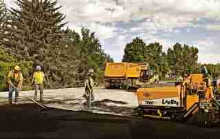 asphalt paving crew with new asphalt and paver with dump truck and skid steer