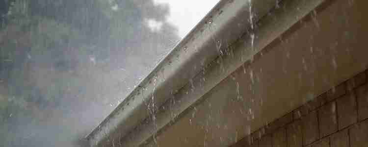 stormy sky with rain falling off roof rain gutter