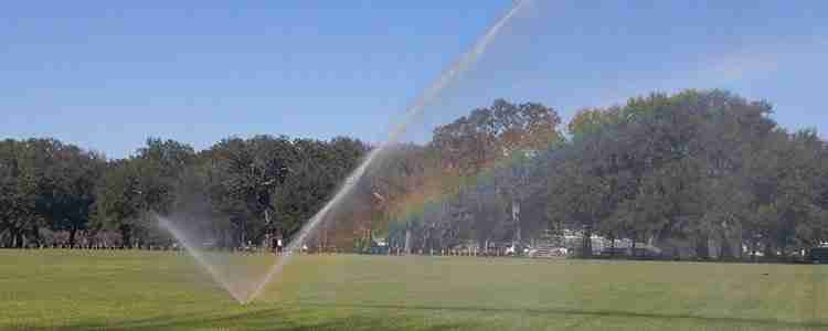 sprinkler in middle of large grassy field with trees