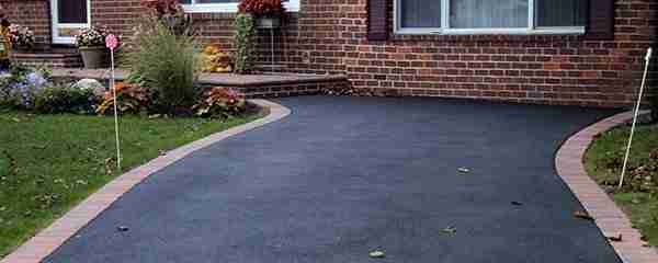 asphalt driveway with brick edges and house in background