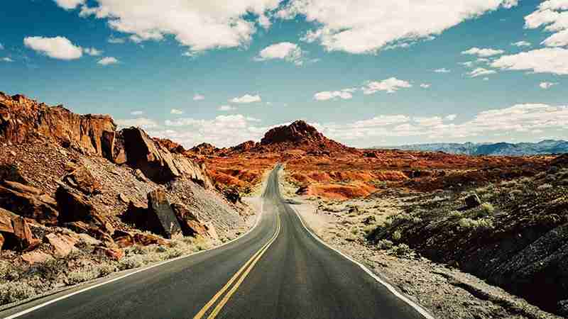 Long asphalt pavement road through rocky desert in the hot summer. Red hills and blue sky with clouds.